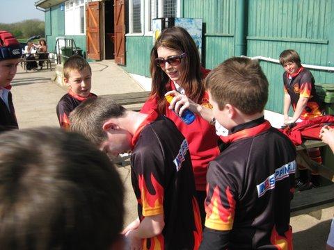 Ms Ann McCarthy applies sun block to the team