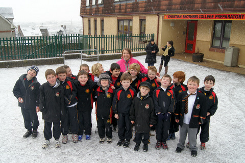First Class with their teacher in the snowy school yard