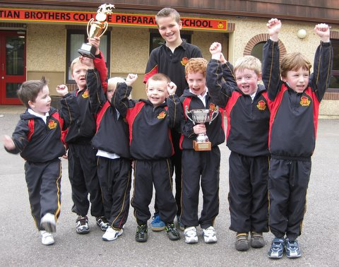 Junior Infants boys hold up some of Tommy's boxing trophies.